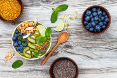 Matcha green tea breakfast superfoods smoothies bowl topped with chia, flax and pumpkin seeds, bee pollen, granola, coconut flakes Royalty Free Stock Images