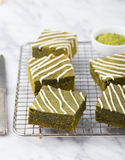Matcha green tea brownie cake with white chocolate on a cooling rack Grey stone background Royalty Free Stock Image