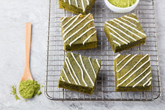Matcha green tea brownie cake with white chocolate on a cooling rack Grey stone background Royalty Free Stock Photo
