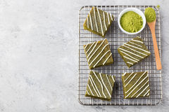 Matcha green tea brownie cake with white chocolate on a cooling rack Grey stone background Top view Copy space Stock Photography