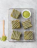Matcha green tea brownie cake with white chocolate on a cooling rack Grey stone background Top view Copy space. Matcha green tea brownie cake with white Stock Photography