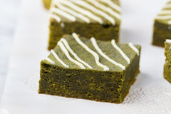 Matcha green tea brownie cake with white chocolate on a white plate. Grey stone background Royalty Free Stock Photo