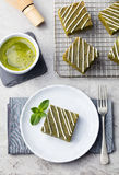 Matcha green tea brownie cake with white chocolate on a white plate Grey stone background Stock Photos