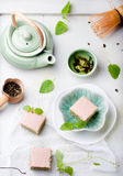 Matcha green tea cakes with white chocolate glaze. And sesame seeds with a cup of green tea and balm, mint leaves on a wooden background Royalty Free Stock Photography