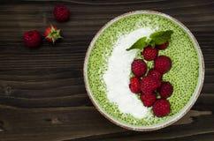 Matcha green tea chia seed pudding bowl, vegan dessert with raspberry and coconut milk. Overhead, top view, flat lay. Matcha green tea chia seed pudding bowl Royalty Free Stock Image