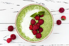 Matcha green tea chia seed pudding bowl, vegan dessert with raspberry and coconut milk. Overhead, top view, flat lay. Royalty Free Stock Photography