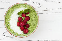 Matcha green tea chia seed pudding bowl, vegan dessert with raspberry and coconut milk. Overhead, top view, flat lay. Royalty Free Stock Image