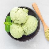 Matcha green tea ice cream balls in a black bowl, top view, square format Stock Image