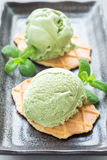 Matcha green tea ice cream balls served with waffles on plate, vertical. Matcha green tea ice cream balls served with waffles on black plate, vertical Stock Photo