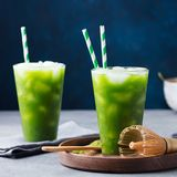 Matcha, green tea ice tea, cocktail in tall glass on wooden plate. Grey stone background. stock images