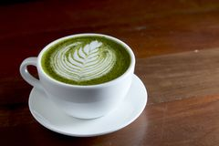 Matcha green tea latte hot drink. Placing on the brown rustic wooden table, with natural light, food dark photography royalty free stock photography