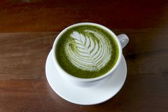 Matcha green tea latte hot drink. Placing on the brown rustic wooden table, with natural light, food dark photography stock image