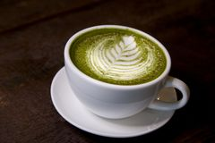 Matcha green tea latte hot drink. Placing on the brown rustic wooden table, with natural light, food dark photography stock images