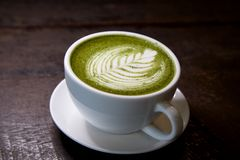 Matcha green tea latte hot drink. Placing on the brown rustic wooden table, with natural light, food dark photography royalty free stock photo