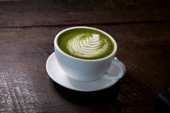Matcha green tea latte hot drink. Placing on the brown rustic wooden table, with natural light, food dark photography royalty free stock photos