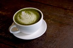Matcha green tea latte hot drink. Placing on the brown rustic wooden table, with natural light, food dark photography royalty free stock images