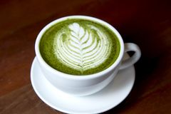 Matcha green tea latte hot drink. Placing on the brown rustic wooden table, with natural light, food dark photography stock photography