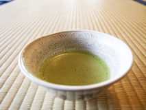 Matcha Green Tea. Is a popular drink in Japan. Here it is served in the traditional style in a bowl on a tatami mat Royalty Free Stock Photography
