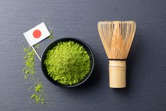 Matcha, green tea powder with bamboo whisk and Japanese flag on slate background. Top view. Stock Photography
