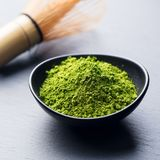Matcha, green tea powder in black bowl with bamboo whisk on slate background. Close up. Stock Photo