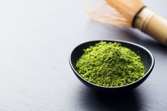 Matcha, green tea powder in black bowl with bamboo whisk on slate background. Copy space. Royalty Free Stock Image