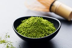 Matcha, green tea powder in black bowl with bamboo whisk on slate background. Copy space. Royalty Free Stock Photos
