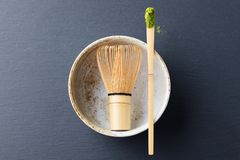 Matcha, green tea powder in black bowl with bamboo whisk on slate background. Top view. Copy space. Stock Photo