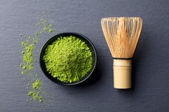Matcha, green tea powder in black bowl with bamboo whisk on slate background. Top view. Stock Images