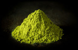 Matcha green tea powder on black cast iron background. Heap of matcha green tea powder on black cast iron background Stock Photography
