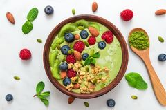 Matcha green tea smoothie bowl with fresh fruits, berries, nuts, seeds and granola with a spoon for healthy breakfast stock photo