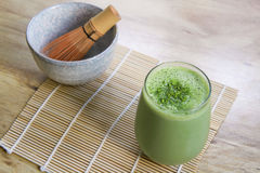 Matcha Green Tea Smoothie with Stone Bowl and wooden whisk on bamboo mat on table Royalty Free Stock Photos