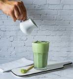Matcha groene thee latte met matchapoeder en houten lepel stock afbeeldingen