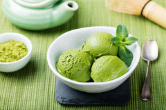 Matcha ice cream in white bowl. Green background. Matcha ice cream scoop in white bowl on a wooden background royalty free stock photo