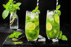 Matcha iced green tea with lime and fresh mint on black stone slate background. Super food drink. Royalty Free Stock Photos