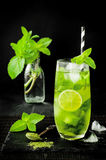 Matcha iced green tea with lime and fresh mint on black stone slate background. Super food drink. Stock Image
