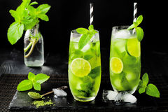 Matcha iced green tea with lime and fresh mint on black stone slate background. Super food drink. Royalty Free Stock Photography