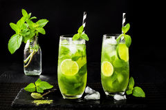 Matcha iced green tea with lime and fresh mint on black stone slate background. Super food drink. Royalty Free Stock Photo
