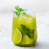 Matcha iced green tea with lime and fresh mint on a marble background. Copy space.  Royalty Free Stock Photos