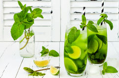 Matcha iced green tea with lime and fresh mint on white rustic background. Super food drink. Stock Photos