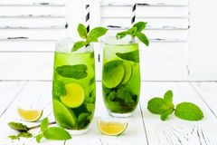 Matcha iced green tea with lime and fresh mint on white rustic background. Super food drink. Royalty Free Stock Photos