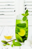 Matcha iced green tea with lime and fresh mint on white rustic background. Super food drink. royalty free stock images