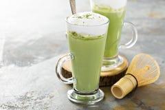 Matcha latte i högväxta exponeringsglas royaltyfri foto