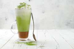 Matcha latte with salted caramel in tall glass. Copy space Stock Image