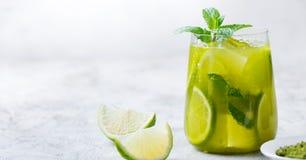 Matcha med is grönt te med limefrukt och den nya mintkaramellen på en marmorbakgrund kopiera avstånd arkivfoto