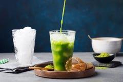 Matcha, té de hielo del té verde que vierte en vidrio alto en la placa de madera Fondo azul gris Imagen de archivo libre de regalías