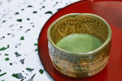 Matcha tea. In a bowl on a white table Stock Photos