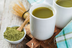 Matcha tea in white bowls. Rustic wood background Stock Photos