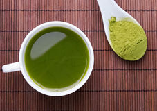 Matcha tea in a white cup on the brown mat Royalty Free Stock Photos