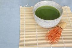 Matcha viftar grönt te i sten som dricker bunken på bambuplacemat med trä Arkivfoton