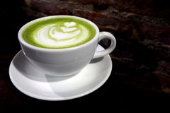 Matcha zielonej herbaty latte filiżanka na ściana z cegieł tle Zdjęcie Stock